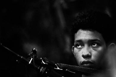 A fifteen year old, after three months of training, on his first day of active military duty as a FARC guerrilla guards a jungle camp in the state of Caquetá, Colombia, 2000.
