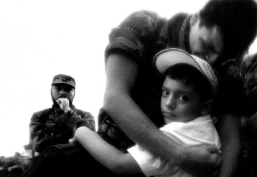 A soldier hugs his son who he has not seen for 3 years as a guerrilla commander looks on during a POW release ceremony in La Macarena, Colombia in 2002.