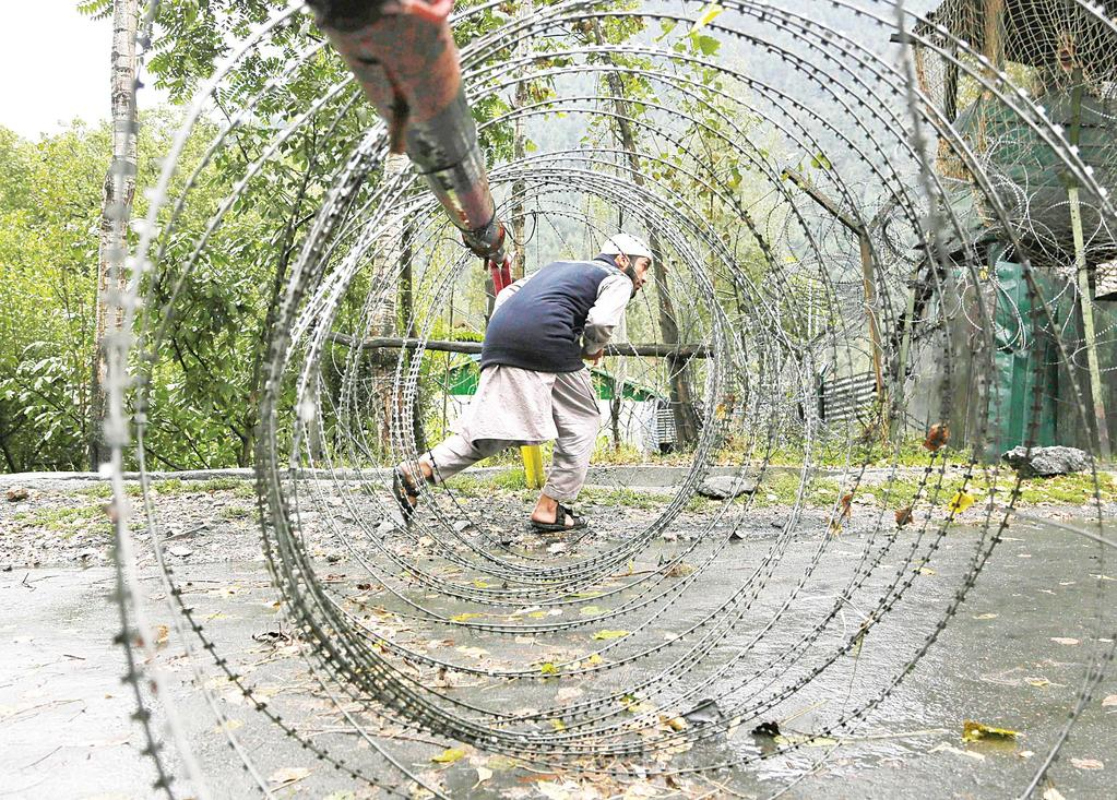 INTERNATIONAL 16 World News Roundup Africa A Kashmiri man ducks to cross an iron barricade with coils of razor wire near a military base at Braripora, near the de facto border dividing Kashmir