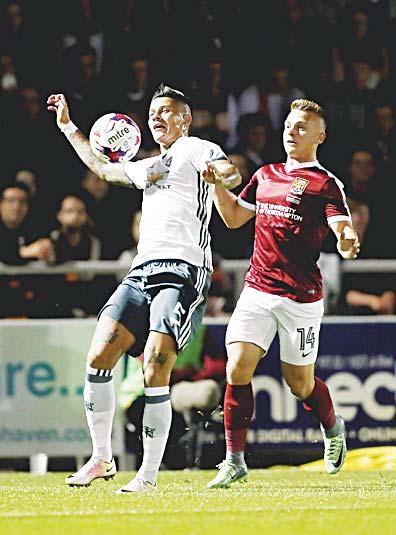 Northampton Town s Sam Hoskins (right), and Manchester United s Marcos Rojo battle for the ball during the English League Cup third round soccer match at Sixfields Stadium, Northampton, England, on