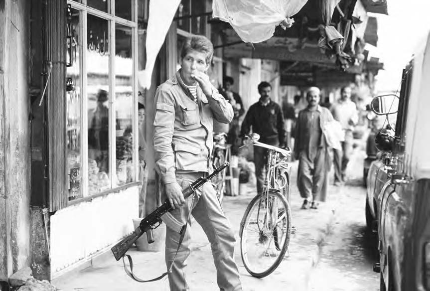 236 SOVIET WAR IN AFGHANISTAN A young Soviet soldier carries an AK-47 rifle on a busy shopping street in Kabul.