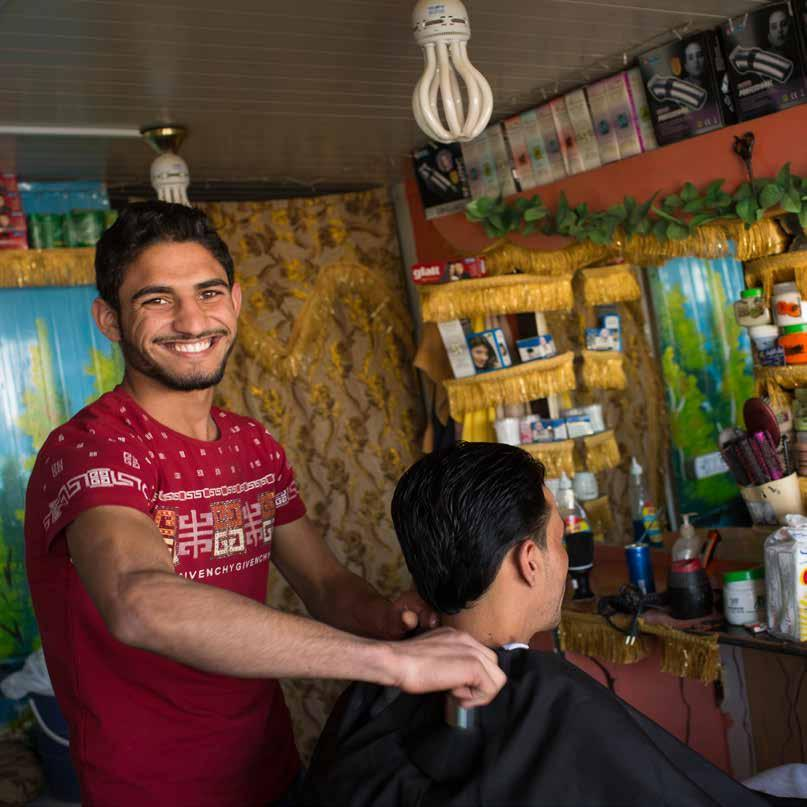 A Syrian barber cuts hair in the shop that he established in