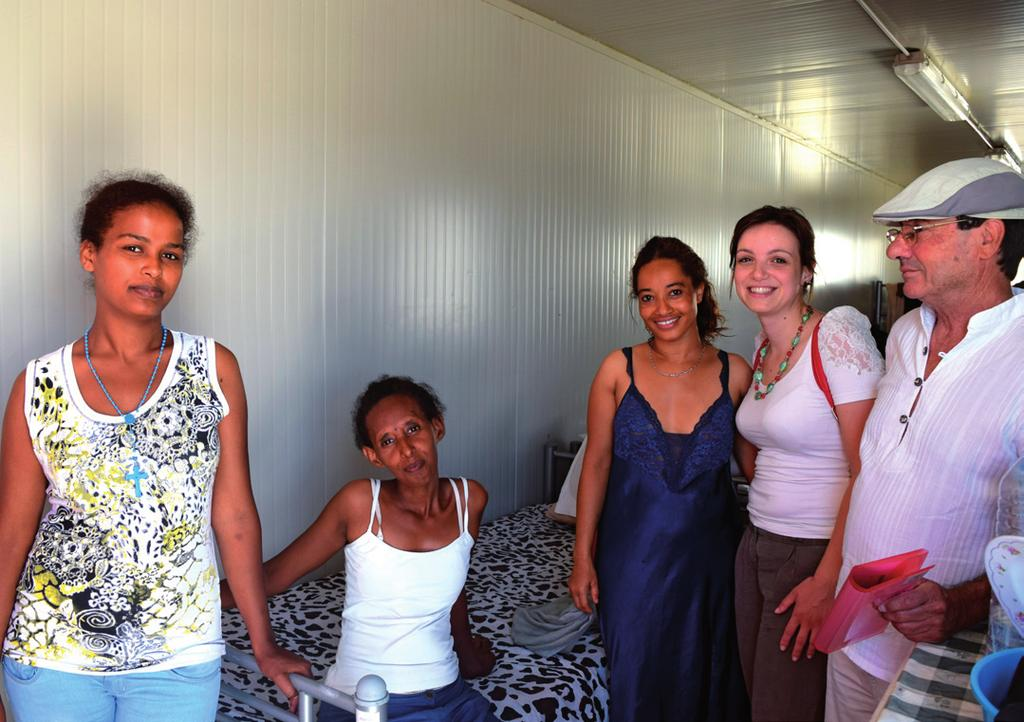 Brother Salvu (R) and lawyer Roxanne Borg (2-R)of JRS Malta are welcomed by three Eritrean women into their container home